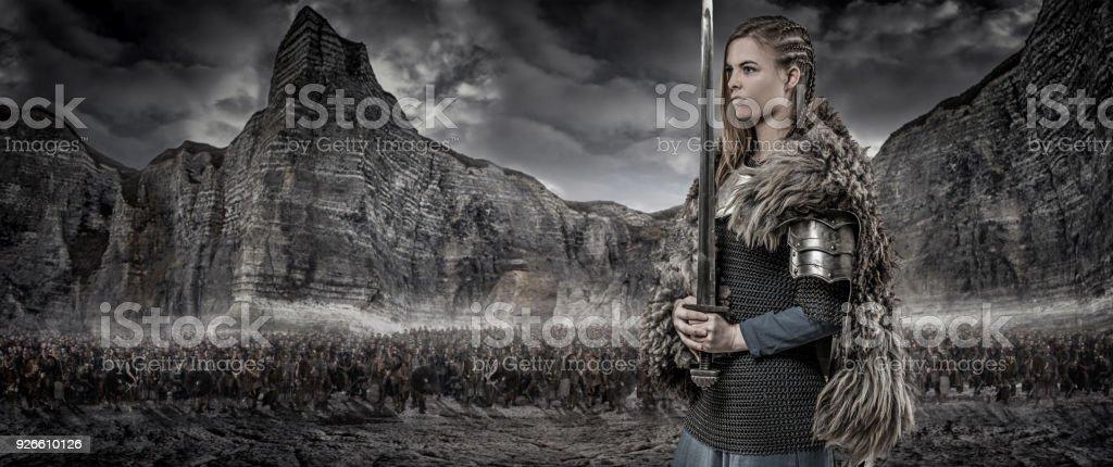 Arma empunhando fêmea de guerreiro viking sozinha na frente do tesouro viking e Cordilheira - foto de acervo