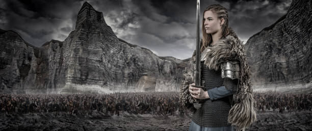 weapon wielding viking warrior female alone in front of viking hoard and mountain range - indumento corazzato foto e immagini stock