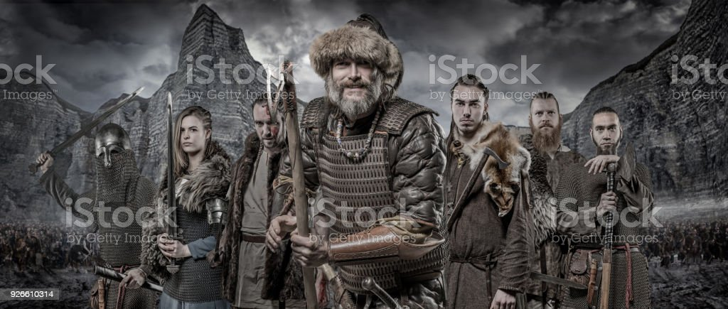 Weapon Wielding Viking Warriors In Formation In Front Of Viking Hoard And Mountain Range Royalty