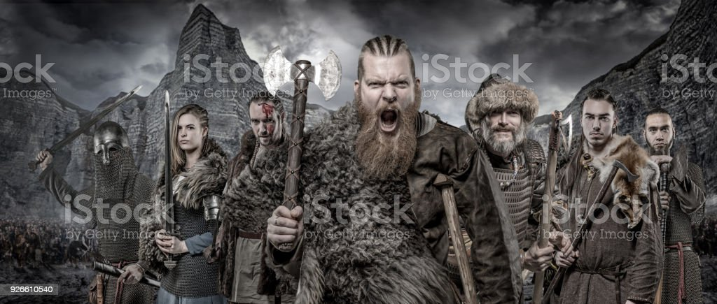 Weapon wielding viking warriors in formation in front of viking hoard and mountain range stock photo