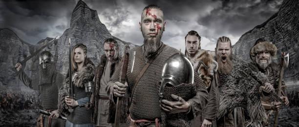 waffe schwingt wikinger-krieger in formation vor viking hort und gebirge - filmplakate stock-fotos und bilder