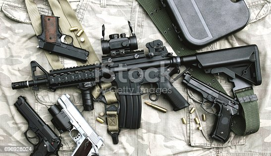 istock Weapons and military equipment for army, Assault rifle gun (M4A1) and pistol on camouflage background. 696928024