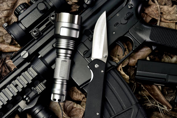 Weapons and military equipment for army, Guns tactical flash light and pocket army knife, Assault rifle gun (M4A1) and 9mm pistol on dry leaves forest background. stock photo
