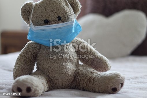 Friendly soft well loved teddy bear encouraging children to wear face protection like him! Teddy is seen sitting in a child's bed wearing his PPE blue face mask. Could be used as preparing for younger children to return back to school, wear face mask like teddy. Focus is on the mask.