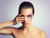 Studio shot of an attractive young woman posing with her face brightly painted