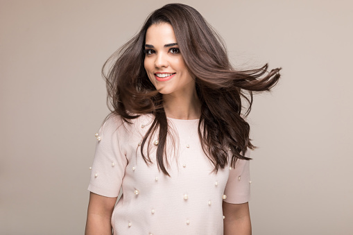 Charming happy woman tossing her hair while standing against colored background