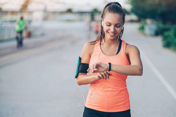 Wearable tech Smiling young sportswoman with arm band and headphones woman taking pulse stock pictures, royalty-free photos & images