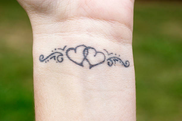 Linked hearts tattoo on wrist Wearer's own design for a linked hearts tattoo which decorates her left wrist. Close up taken in natural daylight. whiteway stock pictures, royalty-free photos & images