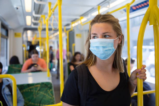 Wearing a Face Mask on the Tram With the spread of coronavirus between people, more and more are wearing face masks in public places covid mask stock pictures, royalty-free photos & images