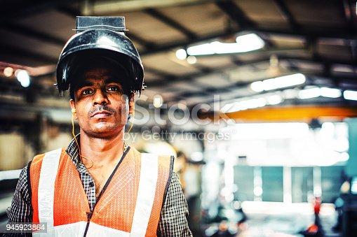 Welder looking towards the camera while standing in his factory. Wearing his mask improperly.
