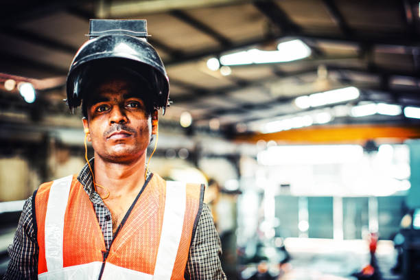 wearing a welder mask while looking at the camera - manufacturing occupation stock photos and pictures