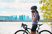istock Wearing covid-19 mask while riding bike. Sport cyclist woman biking putting on face mask for Covid-19 prevention during summer outdoor leisure exercise activity. Fitness outside 1265742899