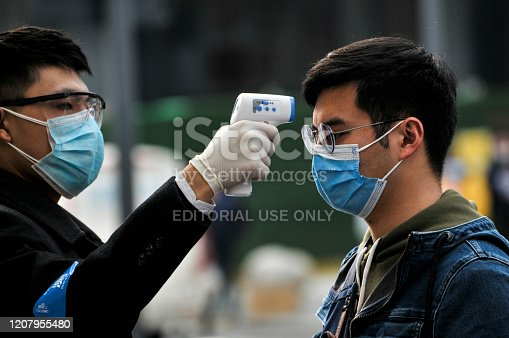 Chengdu/China-Feb.2020: New type coronavirus pneumonia in Wuhan has been spreading into many cities in China. Wearing masks, people lined up for temperature checks before entering the Chunxi Road, downtown mall in Chengdu,China,which is Chengdu's most famous shopping street and has numerous stores for shopping.