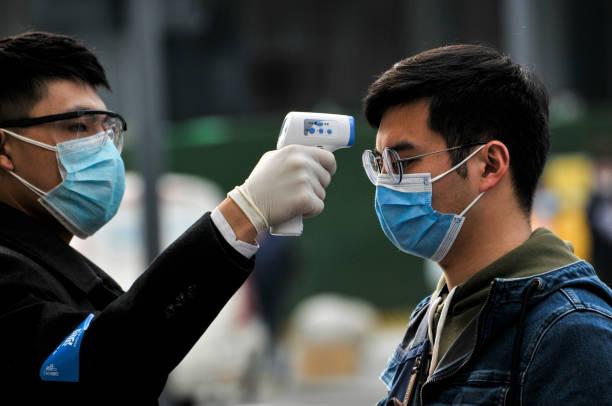 bära masker, människor uppradade för temperaturkontroller innan de går in i köpcentret 、 starbacks och hotell i chengdu, kina - cold street bildbanksfoton och bilder