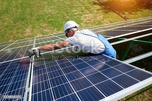 istock Wearing protective helmet, mounter installing solar panels on roof. 1008856320