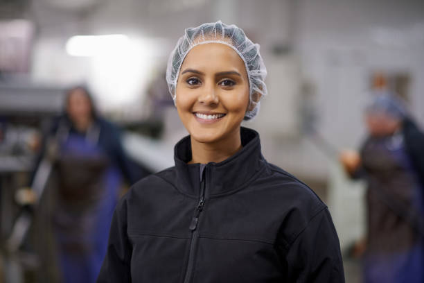 Wearing warehouse fashion Portrait of a happy young factory worker standing in a food processing plant hair net stock pictures, royalty-free photos & images