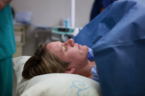 Weary Mother Lies In Anticipation Before Her Caesarian Section Stock Photo - Download Image Now