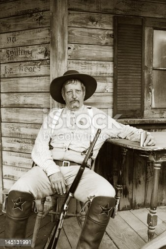 Very somber and tired Caucasian man with sheriff badge sitting on porch holding rifle and flask.  Black and white.   - See lightbox for more