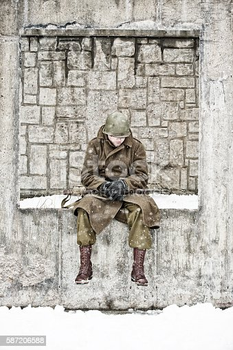 Weary WWII soldier sitting on a wall in a courtyard bundled against the winter snow.