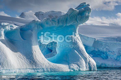 A dramatically shaped and weather eroded iceberg floating in Wilhemina Bay Antarctica with a large hole in the centre glowing blue, and with a distant background of snow and ice covered mountains on a a sunlit summers day