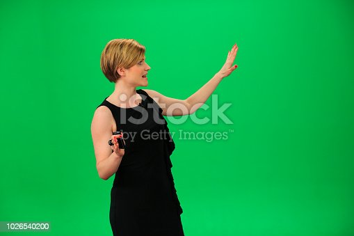 Young asian weather woman in front of a green background with small remote in her other hand.