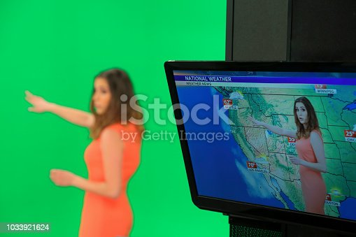 Young weather woman in front of a green background with small remote in her other hand. Weather forecast with map on the tv screen.
