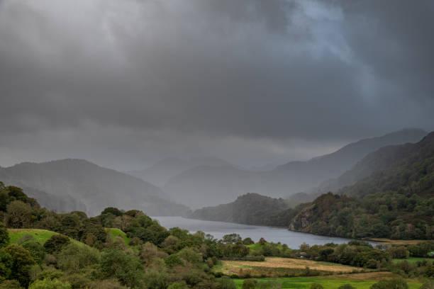 een weer front dat door nant gwynant en een schokkerige llyn gwynant in het snowdonia national park beweegt - caernarfon and merionethshire stockfoto's en -beelden