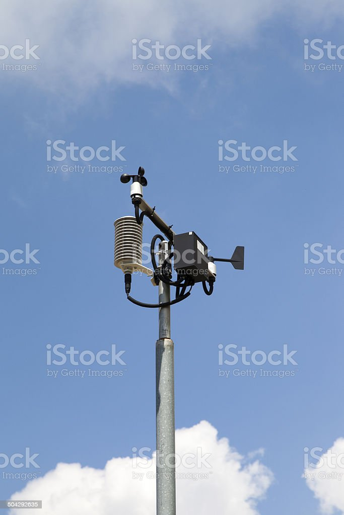 Weather station mast against blue cloudy sky stock photo