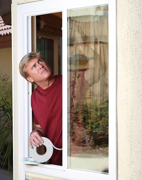 """Weather Stripping Man WS """"Man checks his weather stripping work. Professional model shot in 2011 in Moreno Valley, California."""" undressing stock pictures, royalty-free photos & images"""