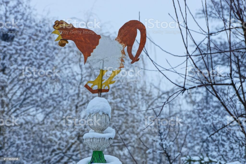 weather vane in the form of a colored iron rooster at the top of the roof stock photo