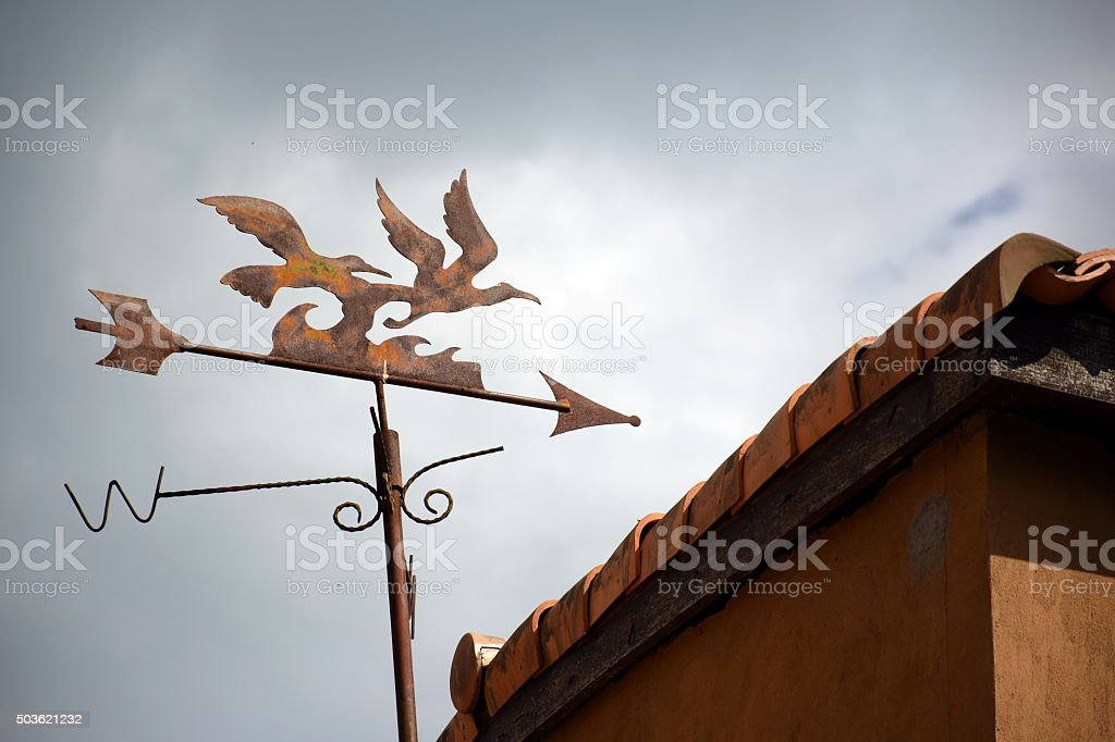 Weather vane on the roof and cloudy sky (vintage filter) stock photo