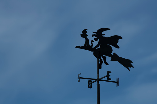Weather vane witch with cat is riding her broomstick southbound