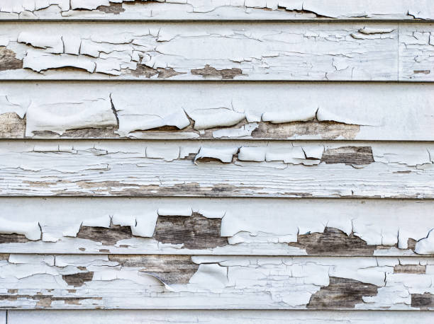 Weathered and chipped gray paint on house exterior stock photo