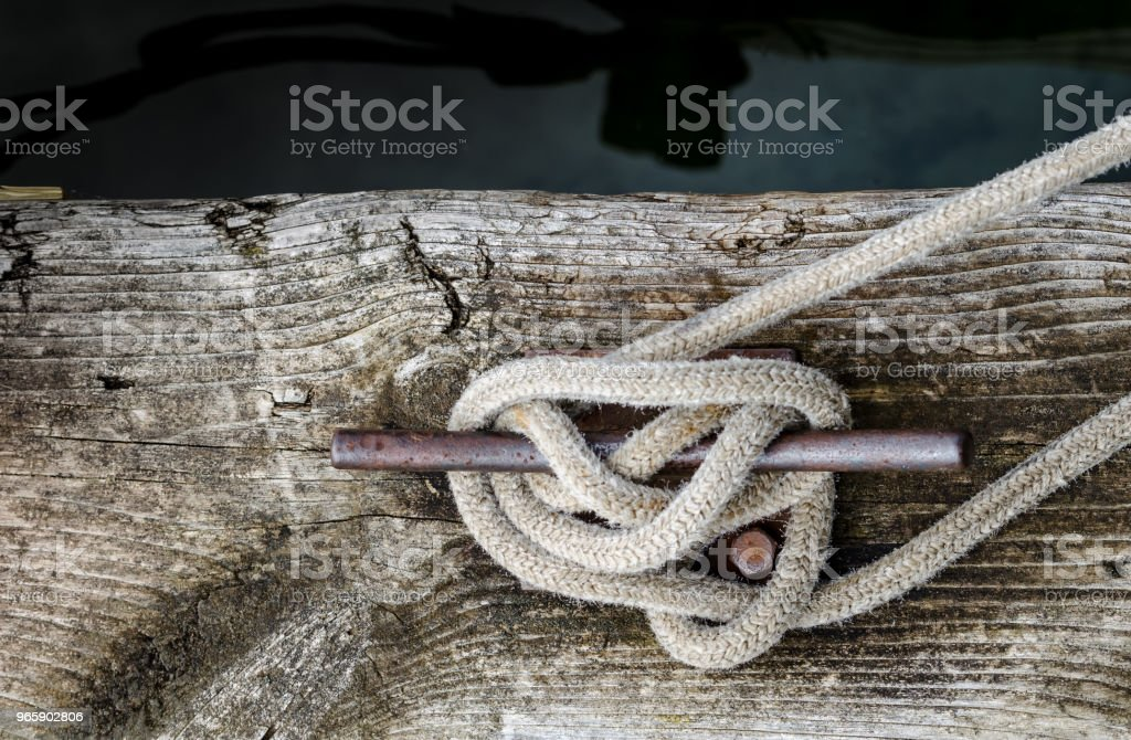 A weathered and grainy old dock board next to the waters edge with an old rope tied to a rusty cleat - Royalty-free Antique Stock Photo