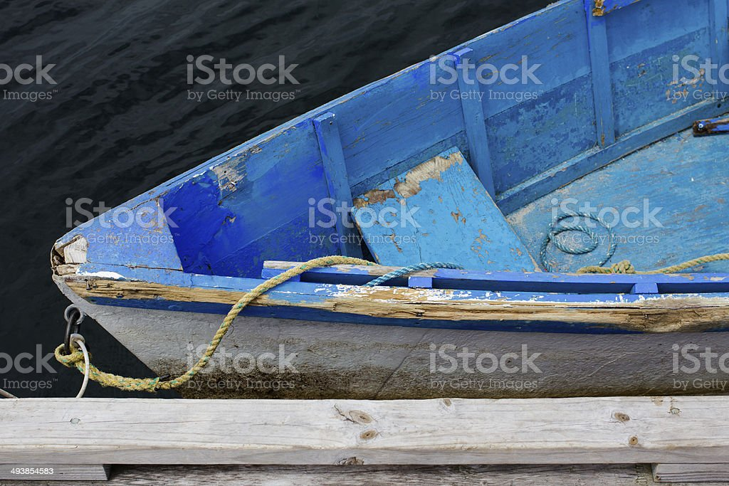 Weathered Blue Wooden Dinghy Rowboat Tied to Dock stock photo