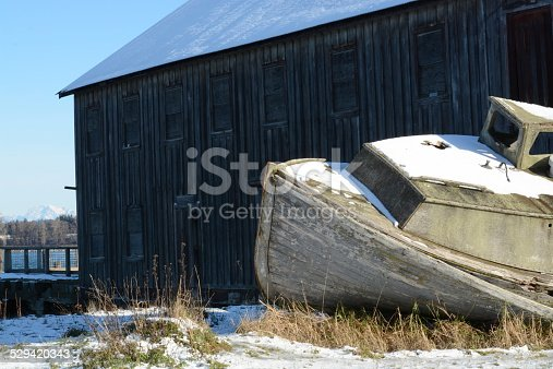 Weathered boat and barn in snow.