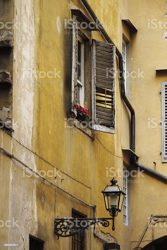 Weathered building with shutters and lamp stock photo