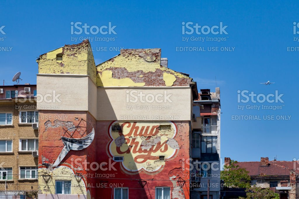 """Weathered Chupa Chups advertising painted on a brick wall Sofia, Bulgaria - May 18 2019: Old advertisement of the brand """"Chupa Chups"""" fading away due to the weather on a brick wall in the city center. Advertisement Stock Photo"""