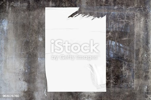 Full-frame weathered concrete wall with a blank poster.