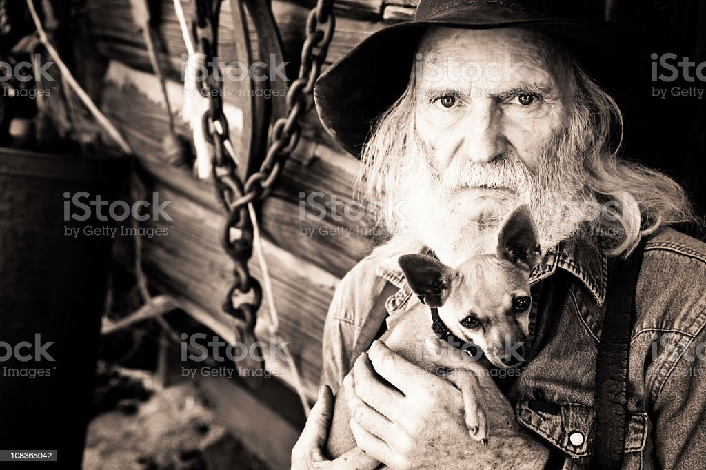 Weathered Cowboy with His Dog stock photo