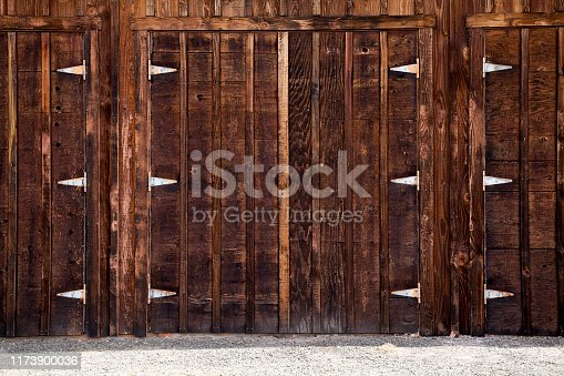 Weathered dark brown barn doors with silver t-hinges.