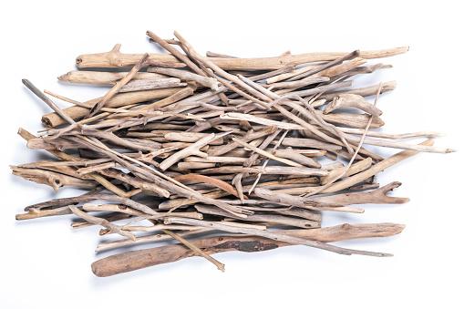 Weathered driftwood sticks heap isolated on white background.