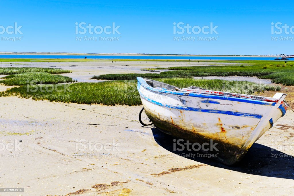 Weathered  fishing boat on the sand at low tide, Ria Formosa Natural Park,Algarve,Portugal stock photo