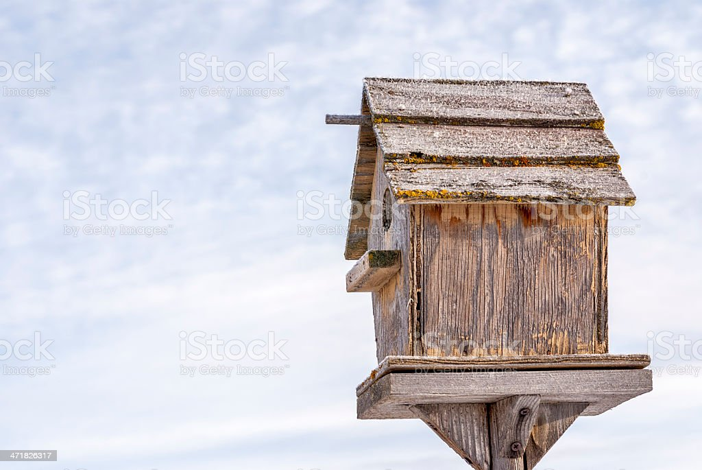 Weathered homemade birdhouse on a stand royalty-free stock photo