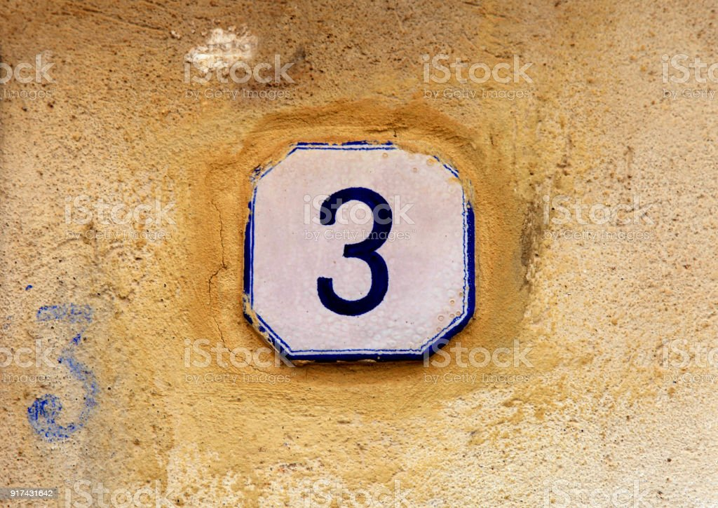 weathered house number 3 (three) stock photo