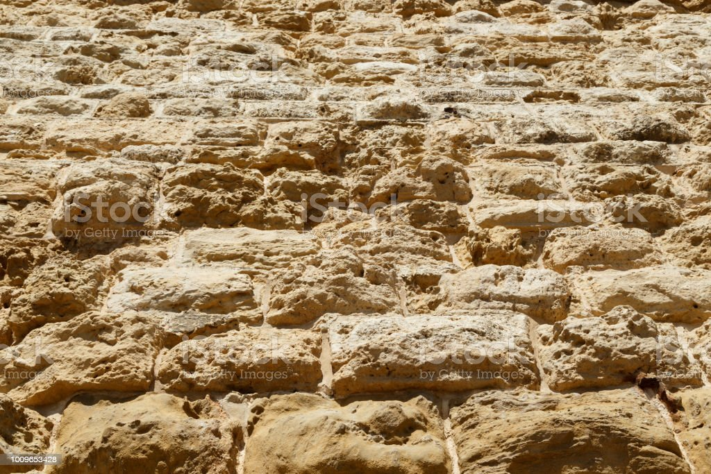 weathered Limestone texture background, blocks make the huge stone walls of the castle of Fort stock photo