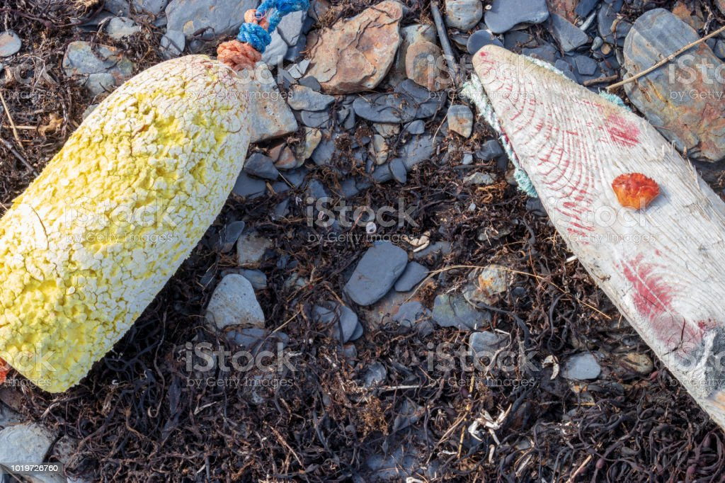 Weathered lobster buoys on a rocky beach with dried seaweed. stock photo
