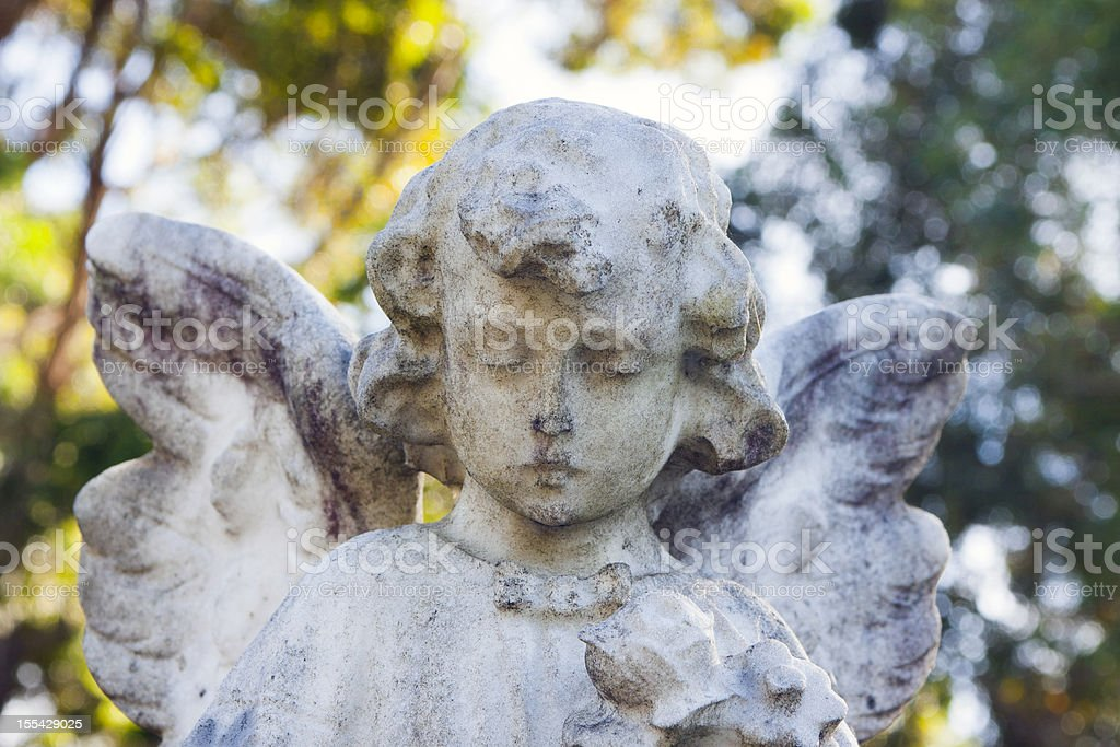 Weathered marble statue of little angel stock photo