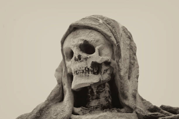 Weathered old Death Sculpture in a Graveyard stock photo