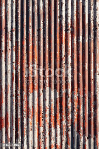 Red paint cracking and peeling on an old corrugated metal surface.